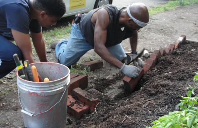 Family working to lay brick edging